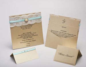 Luxury gold pearlised card wedding invitation with lace and ribbon embellishment