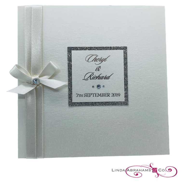bespoke wedding invitation with champagne glitter border and satin ribbon